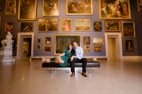 newly engaged couple sitting on a bench in the morgan great hall at the Wadsworth museum of art