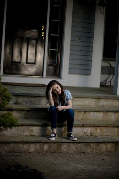 Teen girl sitting on front steps