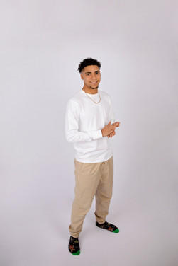 Teen guy in white shirt and khakis in front of white background