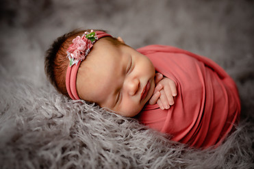 Newborn baby wrapped in pink with a flower headband on a grey fluffy blanket