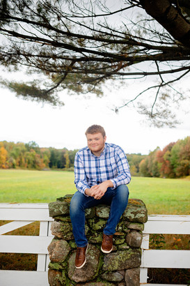 Senior guy sitting on a rock pillar in front of a field