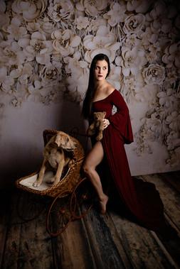 Beige flower backdrop with dog in antique stroller. Stuff animal in hand of women in long dress
