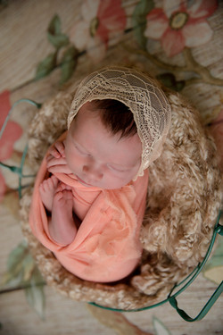 Newborn wrapped in light pink with a bonnet