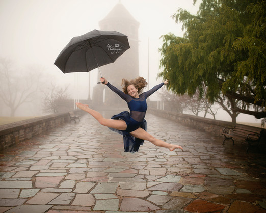 gymnast jumping outside with an umbrella