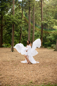 pregnant lady wearing all white in the middle of the woods