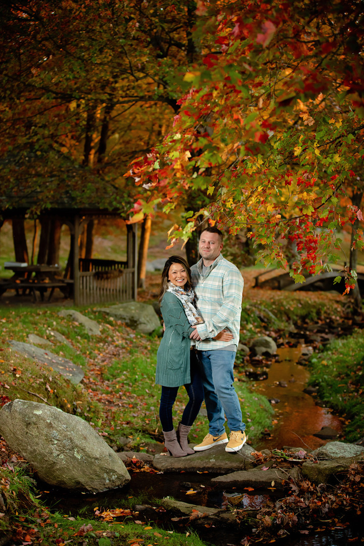 Couple standing by a stream with fall foliage
