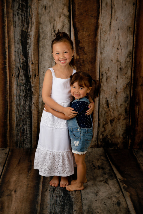 Two sisters standing and hugging