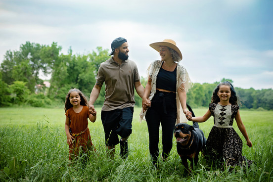family holding hands walking through a field with thier rottweiler