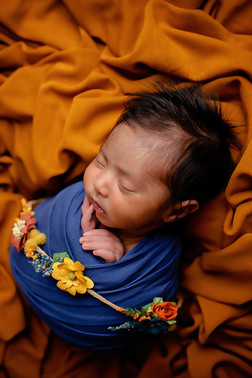 Newborn wrapped in blue with yellow flowers wrinkled backdrop