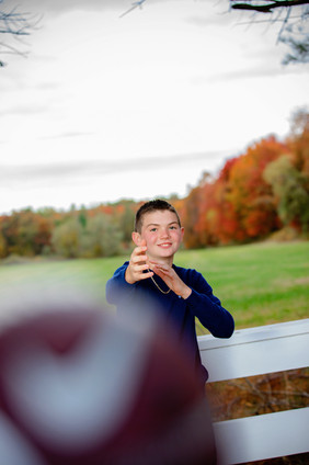 boy throwing a football with a field in the background