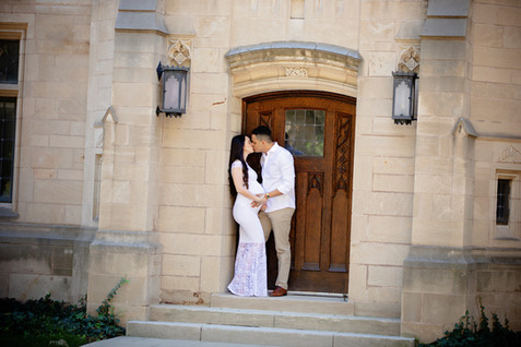 pregnant couple kissing on top of steps