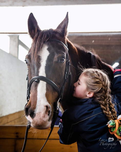 young girl whispering to her horse in his stable