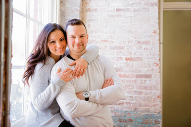 engaged couple with window light in front of whitewashed brick