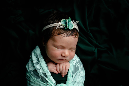 Newborn wrapped in blue with blue flower headband
