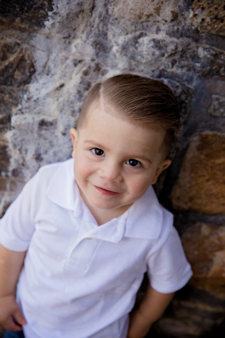 Preschool boy leaning against rock wall