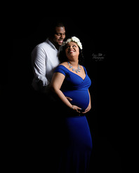Man behind woman holding her pregnant belly with her looking over her shoulder at him