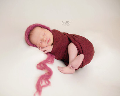 Newborn wrapped in red with pink knit hat