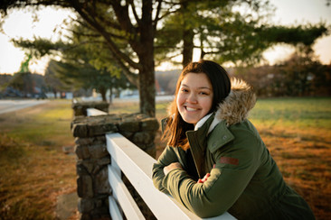 senior girl wearing a jacket leaning on a fence during golden hour