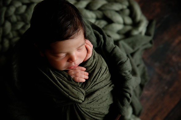 Newborn wrapped in dark green