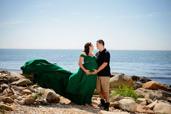 pregnant couple wearing green at beach