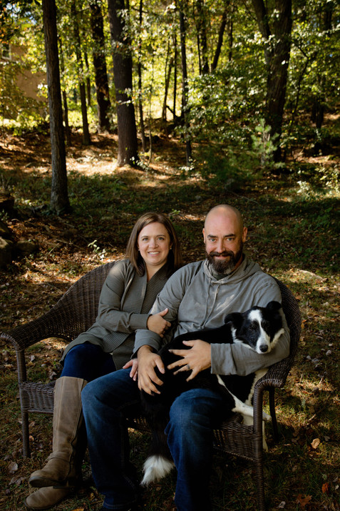 couple sitting on bench in woods with their dog
