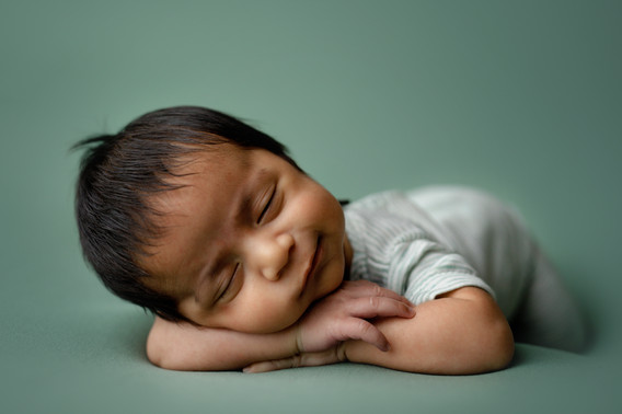 Newborn laying on his belly wearing sleeping outfit.