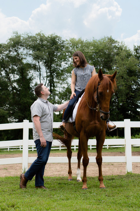 Man standing next to his fiancee who is riding a horse
