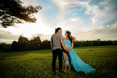 man holding his pregnant wifes bare belly she is wearing a blue flowing maternity dress at sunset