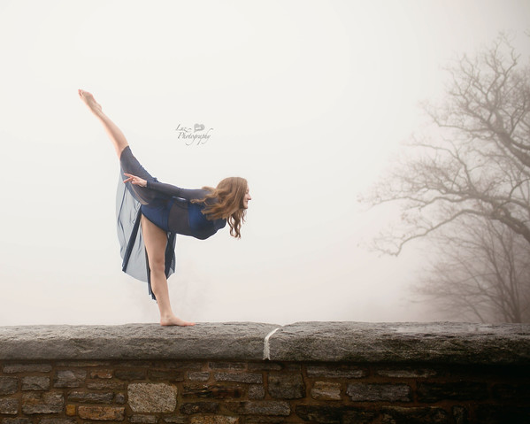 gymnast posing ontop of a stone wall