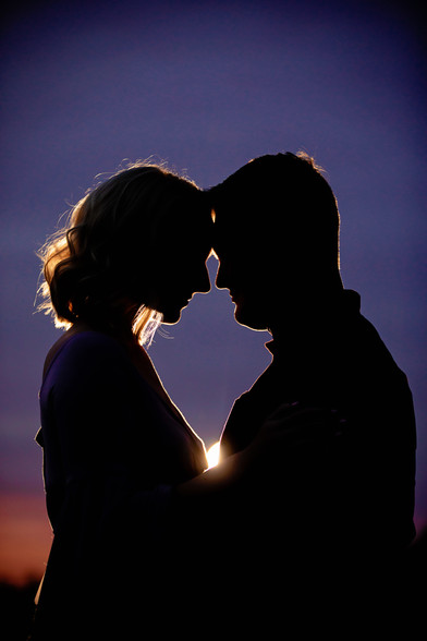 engaged couple silhouette at sunset with purple sky