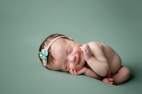 Newborn girl holding cheeks on her side with a green handband
