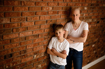 Mom and son both with arms crossed leaning against a brick wall