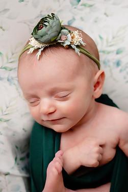 Newborn wrapped in dark green with flower headband