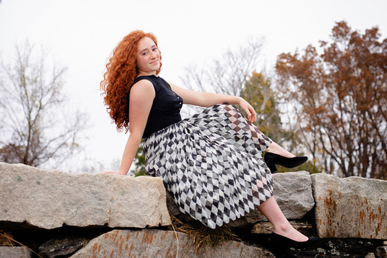 Senior girl redhead in black and white dress sitting on a rock wall