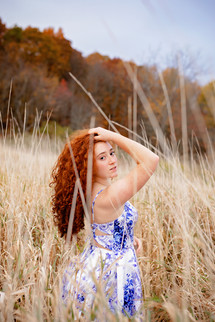 Senior girl with red hair in a blue and white dress standing in a field