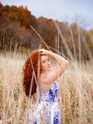 Senior girl with red hair in blue and white dress in a field