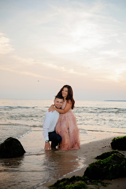 engaged couple sitting on a rock in the water at the beach at sunset