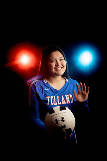 Senior girl in tolland eagles uniform holding volleyball with red and blue lights behind her