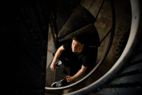 Senior portrait guy in black shirt sitting on a spiral staircase looking up toward the camera