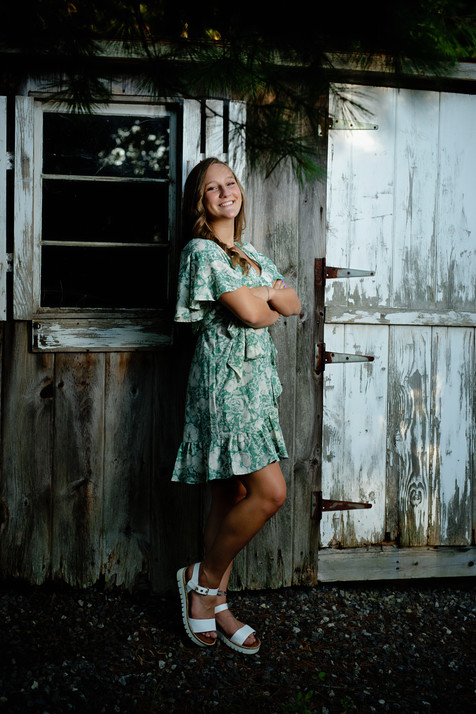 senior girl in a green dress in front of an old shed