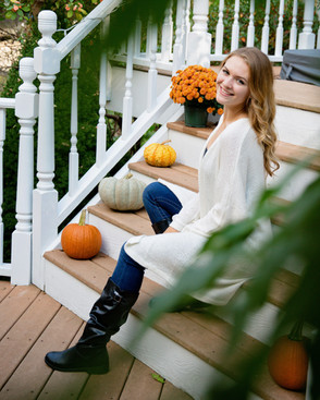 Senior girl in black boots jeans and a white sweater sitting on front steps