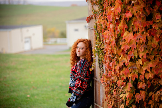Senior girl with red hair leaning against a silo with ivy foliage