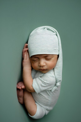 Newborn boy laying on his side on top of his hands in a sleeping outfit