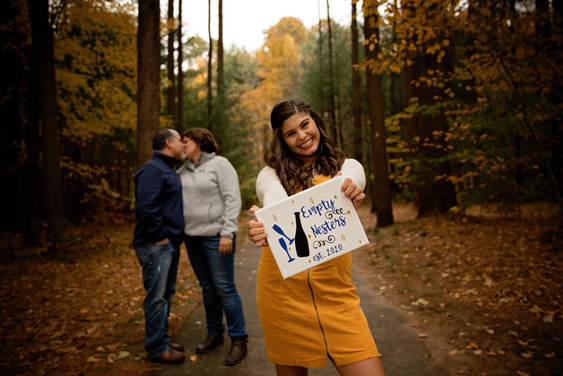 senior girl holding empty nester sign in front of kissing parents