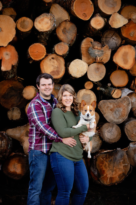 engaged couple holding a corgi in front of a large wood pile