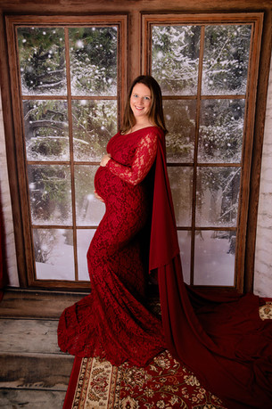pregnant woman in red maternity dress in front of snowy window