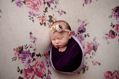Newborn girl laying a flower backdrop