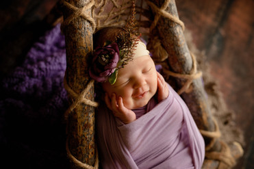 Newborn baby with her hands on her cheeks wrapped in purple on rustic boho hammock