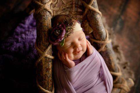 Newborn wrapped in lavander with purple flower
