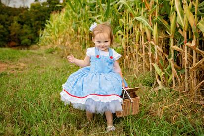Kid walking in grass dressed as Dorthy